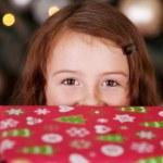 hravá holčička s vánoční dárek — Stock fotografie