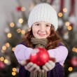 Cute young girl holding out a Christmas bauble — Stock Photo #27477831