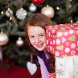 Playful girl peering around stacked gifts — Stock Photo