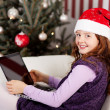 Smiling girl in a Santa hat with a laptop — Stok fotoğraf