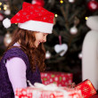 Little girl unwrapping Christmas gifts — Stock Photo #27478653