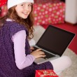 Little girl using a laptop amidst Christmas gifts — Stock Photo