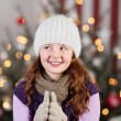 Girl in a woolly cap with a Christmas tree — 图库照片