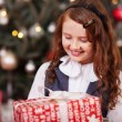 Foto Stock: Happy little girl holding a Christmas present