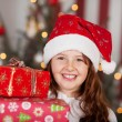 Smiling girl in a Santa hat with her gifts — Stock Photo