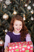 Laughing little girl holding a Christmas gift — Foto de Stock