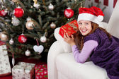 Smiling little girl in front of a Christmas tree — Stockfoto