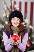 Beautiful young girl with a Christmas bauble — Stok fotoğraf