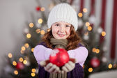 Cute young girl holding out a Christmas bauble — Stock Photo