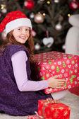 Joyful girl with a large red Christmas gift — Stock Photo