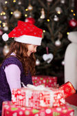 Little girl unwrapping Christmas gifts — Stock Photo