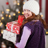 Laughing girl carrying Christmas gifts — Stock Photo