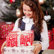 Little girl looking at her Christmas gifts — Stock Photo