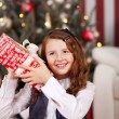 Curious little girl shaking her Christmas gift — Stock Photo