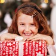 Smiling young girl with a red Christmas present — Stock Photo #27480331