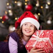 Little girl holding her Christmas gift — Stock Photo #27480351