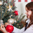 Happy girl hanging Christmas baubles — Stock Photo #27480715