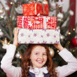 Laughing girl with Christmas gifts on her head — Stock Photo