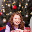 Joyful little girl with a Christmas gift — Stock Photo