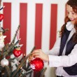 Smiling young girl decorating the Christmas tree — Stock Photo
