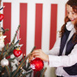 Stock Photo: Smiling young girl decorating the Christmas tree