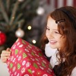 Excited little girl holding a Christmas gift — Stok fotoğraf