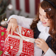 Excited little girl undoing her Christmas present — Stock Photo #27481479