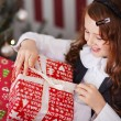 Stock Photo: Excited little girl undoing her Christmas present