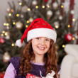 Foto Stock: Beautiful laughing girl in a Santa hat