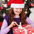 Young girl unwrapping her Christmas present — Stock Photo