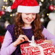 Stock Photo: Young girl unwrapping her Christmas present