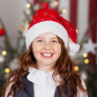 Excited young girl in a red Santa hat — Stock Photo