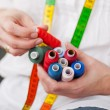Designer Holding Colorful Bobbins — Stock Photo #27486671