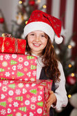 Girl carrying a pile of Christmas gifts — Stock Photo
