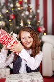 Curious little girl shaking her Christmas gift — Stockfoto