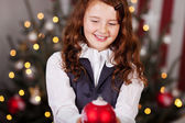 Smiling girl with a Christmas ball — Zdjęcie stockowe