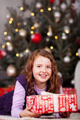 Joyful little girl with a Christmas gift — Stok fotoğraf