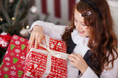 Excited little girl undoing her Christmas present — Stock Photo