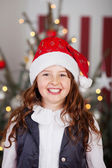 Excited young girl in a red Santa hat — Stok fotoğraf
