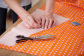 Designer'S Hands Attaching Pin To Cloth In Workshop — Stock Photo