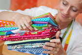Seamstress choosing a fabric — Stock Photo