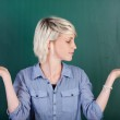 Woman With Empty Palms Against Chalkboard — Stock Photo