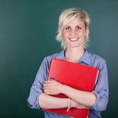 Woman With Folder In Front Of Chalkboard — Stock Photo