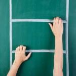 Woman's hand climbing ladder drawn on green board — Stock Photo #27586491