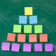 Colorful pyramid made of blank note papers stuck on blackboard — Stock Photo