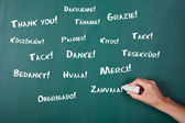 Woman's hand writing Thank You in various languages on chalkboar — Stock Photo