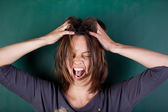 Frustrated woman with hands in hair screaming against chalkboard — Stock Photo