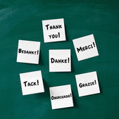Sticky notes with Thank You written in various languages on blac — Stock Photo