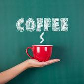 Woman's hand holding coffee cup with coffee written on chalkboar — Stock fotografie