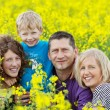 Smiling family between rape flowers — Stock Photo #27667933